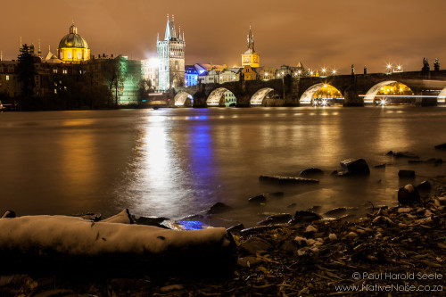 Vltava river and the Charles Bridge on a snowy night in Prague